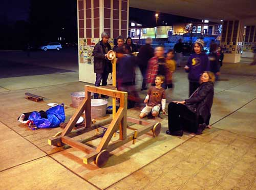 Parents and students try out a medieval catapult.