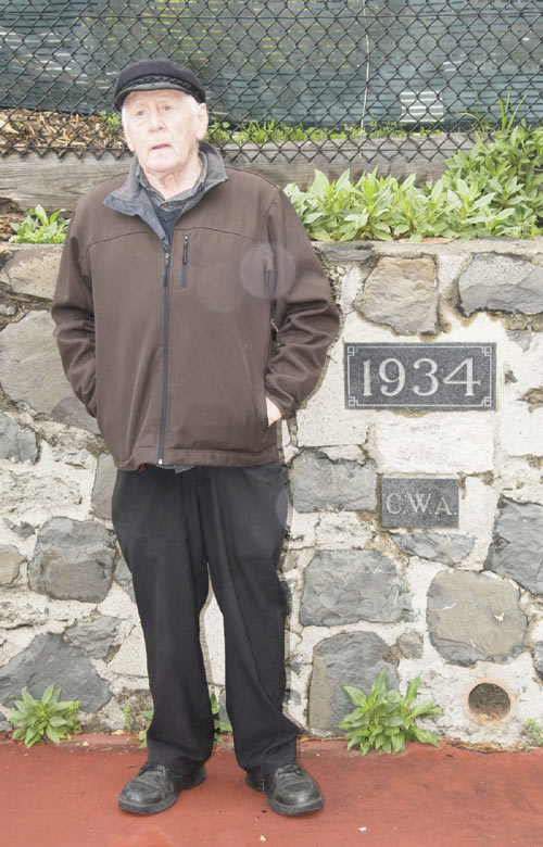 Harry Brill stands next to the stone carvings proclaiming the work of the Federal Civil Works Administration inset in a low wall adjoining the Codornices Park tennis courts, just north of the Berkeley Rose Garden.