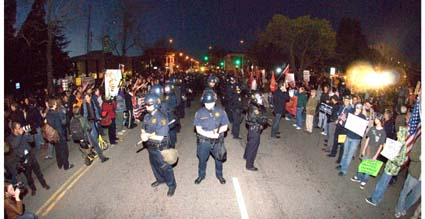 Police in riot gear stand in the middle of Martin Luther King Jr. Way, dividing the opposing protesters.