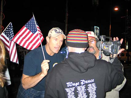 A Move America Forward supporter with an American flag and a veterans cap has a heated exchange with a vet from Veteran's for Peace early Tuesday morning in Civic Center Park at the beginning of a day of debate over the war and the downtown Marine Recruiting Center in Berkeley.