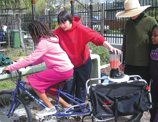 Malcolm X Elementary School fifth grader Anala Griffin makes a strawberry smoothie by pedaling on a bicycle blender during the school's Cesar Chavez Day celebrations Friday, as an AmeriCorp vounteer and Malcolm X garden teacher Rivka Mason look on.