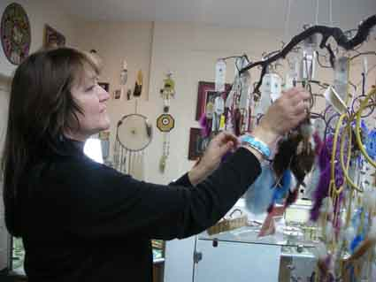 Pennie Opal Plant of Gathering Tribes on Solano hangs up dream catchers made by two Ojibway sisters who live across the border in Canada.