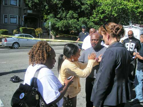 A police officer (at right) talks to people identified by police as friends and family of the shooting victim.
