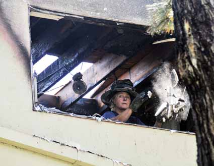 A firefighter tosses a shovelful of broken wallboard out the window of a third-floor apartment in the 2300 block of Russell Street Tuesday afternoon. Layers of aluminum, melted by the intense flames, formed metallic icicles visible on the drainpipe and the bottom of the window frame.
