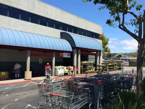 A shopper leaves Berkeley's Grocery Outlet, proposed for demolition for new project.