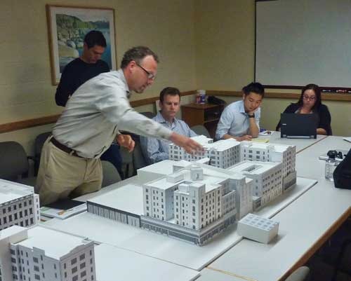 Mark Rhoades points out a detail on the study model of the Acheson Commons block.