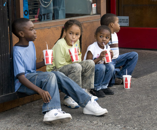 Four young family members take a break for some cool refreshment on Berkeley's Telegraph Avenue during a warm summer afternoon.