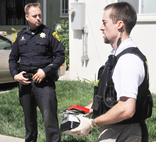 A law enforcement officer carries computer drives and discs seized during Wednesday