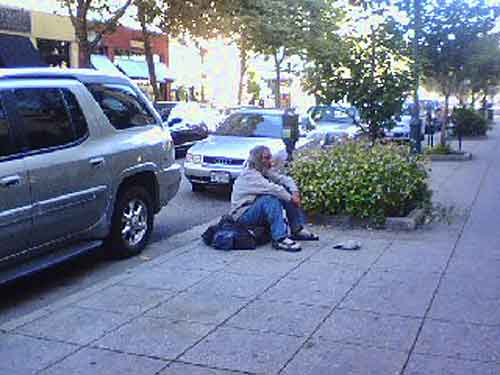 Sitting the sidewalk on Pacific in Santa Cruz, a man whose sign describes him as a veteran begs passersby for money.  Sitting on the sidewalk is illegal in Santa Cruz, but the law is seldom enforced.