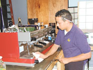 Lupe Vasquez wipes up coffee grounds after making espresso at Cafe Elodie on Shattuck Avenue.  Prices for coffee will go up if voters approve a measure in November that would require stores to sell only certified organic, shade grown or Fair Trade beans.