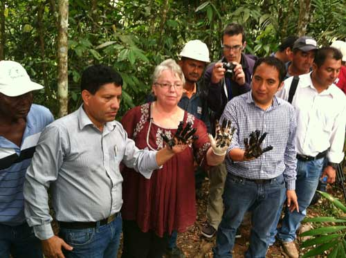 Richmond Mayor Gayle McLaughlin in Ecuador with two local mayors,  with toxic sludge from pools left by oil producers.