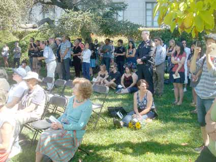 Many of the attendees gathered in the shade at the back of the outdoor