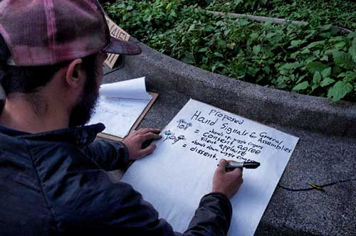 "Second night facilitator at Wall Street protest prepares instructional chart with hand signals for ""general assembly."""
