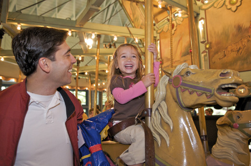 East Bay Regional Park District Regional Parks Foundation Board member William Acevedo takes his daughter for a ride at the recently renovated Tilden Park Carousel.