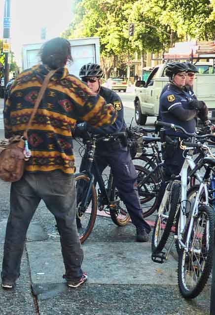 Berkeley Police bicycle patrol waited for the march down Telegraph Avenue and attracted the attention of perennial Berkeley protestor, Zachery Running Wolf.