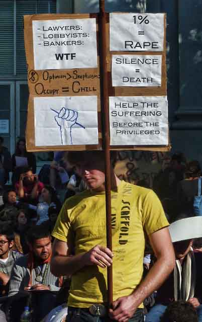"A multi slogan sign, including ""Help The Suffering BEFORE the Privileged."""