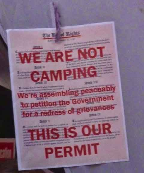 "A flyer put up on the tents.  ""We Are Not Camping. This Is Our Permit"", against a backdrop of the Bill of Rights, highlighting ""We're assembly peaceably to petition the Government for a redress of grievances."""