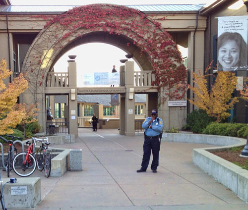 A UC Police officer guards the entrance to Haas School of Business after the shooting.