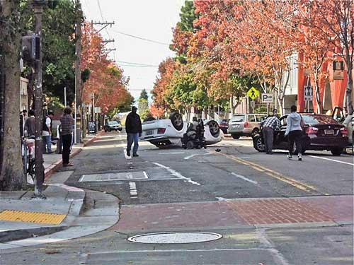 Saturday, 11a.m. moments after Mustang (center) flips out after grazing maroon car (right) which was reportedly emerging from parking space at Channing and Telegraph. Man in wheel chair, center comes to aid of Mustang Driver.