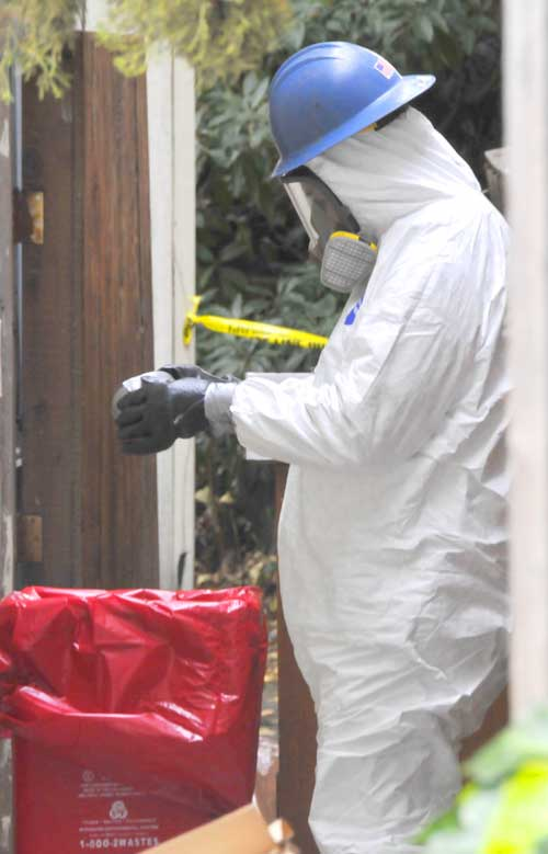 A private crime scene cleanup technician finishes donning his protective gear Thursday afternoon as he prepares to work on the Ashby Avenue room where police found a body buried behind a wall.