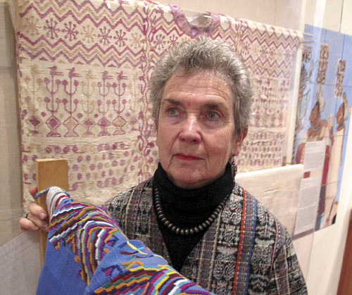 Margot Schevill, curator of the exhibit of Mayan textiles at the Hearst Musuem, stands in front of the display of a white and red Mayan ceremonial blouse from the 1930s.