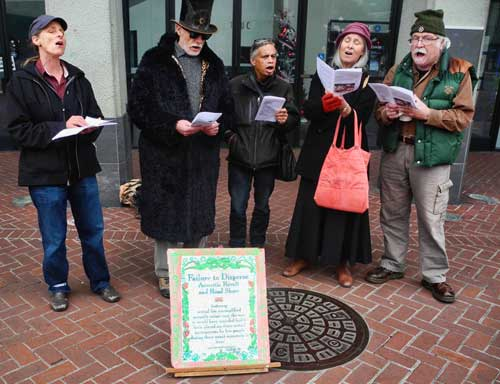 A group of local activists (and occasional bystanders) joined in song to sing anti-Downtown Berkeley Association Christmas carols in the BART Plaza in an effort to bring awareness to the privatization of public space on Sunday, December 16th, 2012.
