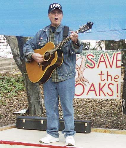 "Country Joe McDonald led celebrants in a chorus of the ""Hokey Oaky"" Saturday, his own version of the venerable children's song with the words tweaked to support the tree-sitters protesting the removal of coast live oaks from a campus grove. Photograph by Richard Brenneman."